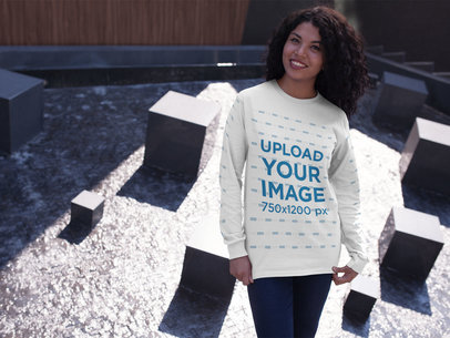 Smiling Woman Wearing a Long-Sleeve T-Shirt Mockup While at an Urban Structure a15976