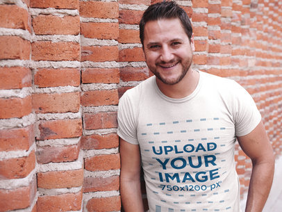 Smiling Dude Wearing a Tshirt Mockup While Lying Against a Bricks Wall a15998