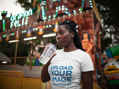 Girl Drinking a Cold Beverage While Wearing a Tshirt Mockup at an Amusement Park a15961