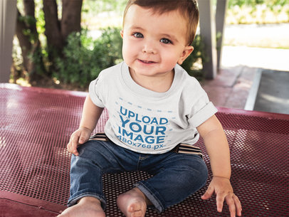 Little Baby Looking to the Camera Wearing a T-Shirt Template While Sitting Down a16090