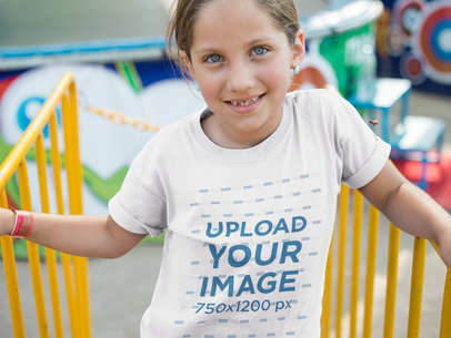 Little Smiling Girl Wearing a T-Shirt Mockup While waiting on an Amusement Park Line a16161