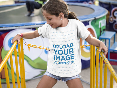 Little Girl Wearing a Round Neck Tee Mockup While at a Yellow Railing a16169