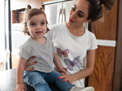 Young Mom with her Baby in the Kitchen Wearing Different Round Neck T-Shirts Mockup a16077