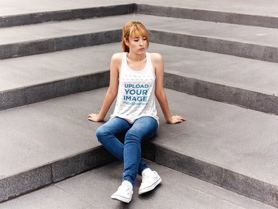 Serious White Girl Wearing a Bella Flowy Tank Mockup While Sitting on Concrete Stairways a16124