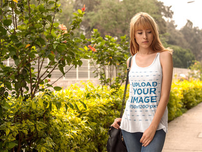 Blonde Girl Wearing a Bella Flowie Tank Top Mockup While Walking in a Garden a16111