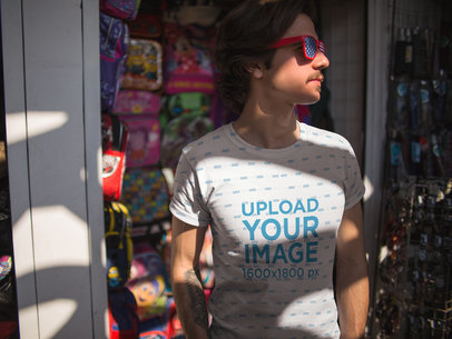 Mockup of a Dude Wearing a Sublimated Tee Template and American Flag Glasses While at a Store a15364