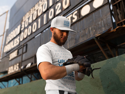 Man Wearing a Baseball Hat and a Raglan T-Shirt Mockup While Looking at his Glove Against a Board a16239