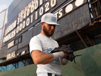 Man Wearing a Baseball Hat and a Raglan T-Shirt Mockup While Looking at his Glove Against a Board a16239