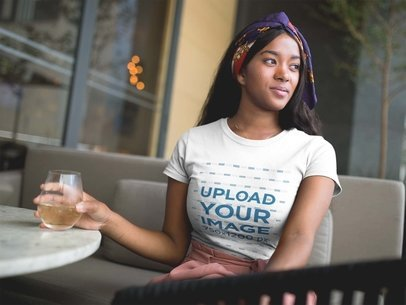 Pretty Woman Having a Drink at a Terrace While Wearing a T-Shirt Mockup a17132