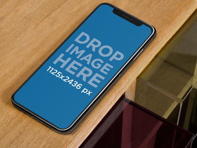 iPhone X Mockup Lying on the Edge of a Wooden Table a17629