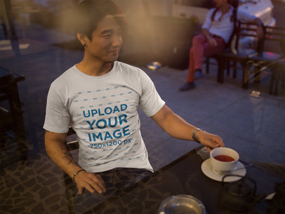 Through the Window Mockup of an Asian Man Wearing a Tshirt at a Cafe a17834