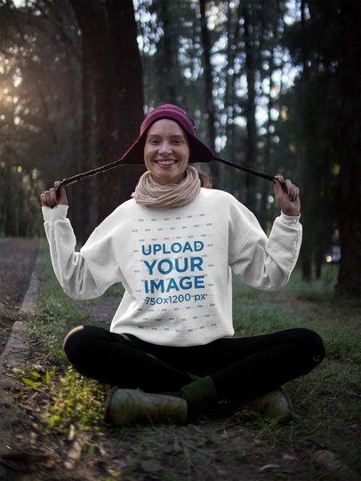 Girl Wearing a Crewneck Sweatshirt Mockup and a Purple Beanie in the Woods a17916