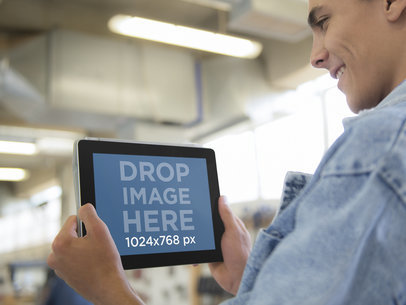 Man Using a Black iPad at Industrial Warehouse Stock Photo Template