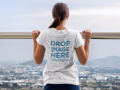 T-Shirt Mockup of a Young Woman Looking Over a Balcony a7989