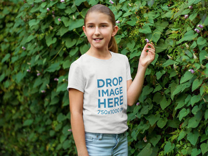 Young Girl Standing Next to a Green Wall T-Shirt Mockup a7923
