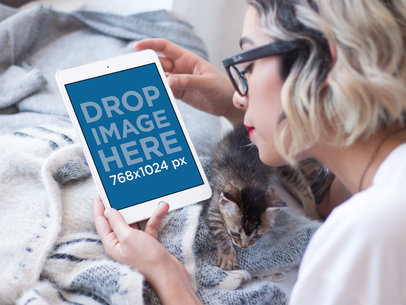 Young Woman with Glasses on her iPad Mini Mockup in Bed with her Cat a12810