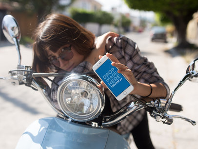 Young Woman on a Motorcycle Showing her iPhone 6s in Portrait Position Mockup a12937wide