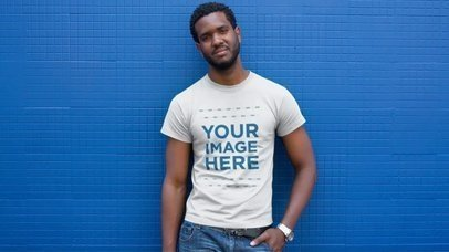 T-Shirt Mockup Video of a Young Black Man Standing in Front of a Blue Wall a12120