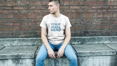 Trendy Guy Sitting in a Downtown Street Wearing a Simple Round Neck Tee Mockup Video a12231-121916