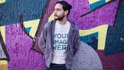 Trendy Guy with a Hoodie and Round Neck T-Shirt Leaning Against a Graffiti Street Wall a13440-122916