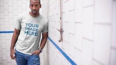 Black Man Lying Against a Wall Wearing a T-Shirt Video Mockup a13121
