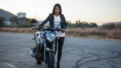 Smiling Biker Girl Wearing T-Shirt and Leather Jacket Outdoors Stop Motion Mockup a13581
