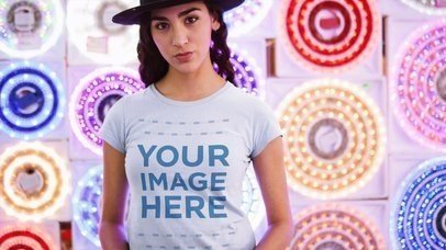 Trendy Girl Wearing a Round Neck Tee and a Hat Against Flashing Circle Lights Cinemagraph Mockup a13326