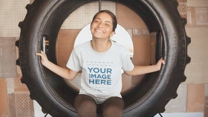 Video Mockup of a Girl Sitting Inside a Big Truck Wheel Making Faces With a T-Shirt a13070