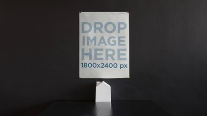 Stop Motion Mockup Of A Poster On A Black Wall While Paper Chimney Moves b13646