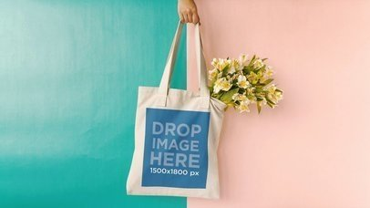 Hand Swinging Tote Bag Against Green And Pink Background With Flower Mockup Stop Motion a13664