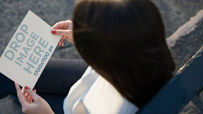 Video Of A Girl Looking At A Flyer While Sitting Down Waiting Mockupa13915