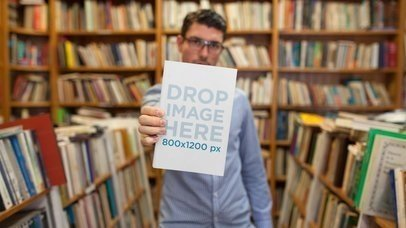 Mockup Of A Young Man At A Library Holding A Book On His Hand Shows It To You Stop Motion a13853