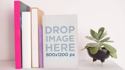 Book Standing On A White Surface Against Other Books While A Plant Rotates Nearby Stop Motion Mockup a13865
