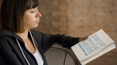Video of a Short Haired Girl Holding a Book in Her Hand While Sitting down Mockup a14064