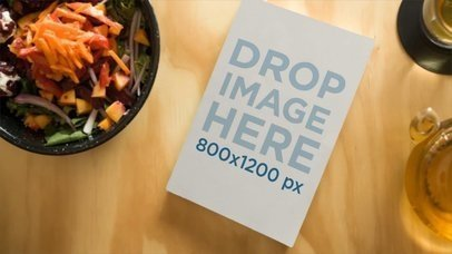 Video of a Book Lying on a Wooden Table with Healthy Food Surrounding It a14176