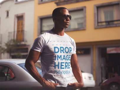 Young Black Man Wearing a Short Sleeved Round Neck T-Shirt and Sunglasses While Staring at the City Mockup a14220