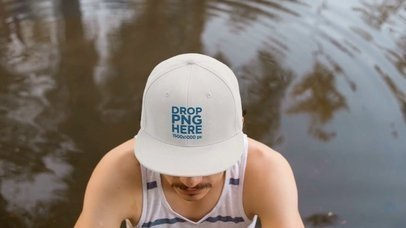 Video of a Young White Man Wearing a Hat While near a Lake a14162