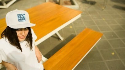 Video Mockup of a Young Hispanic Girl Wearing a Snapback Hat While Sitting in a Cafeteria a14206