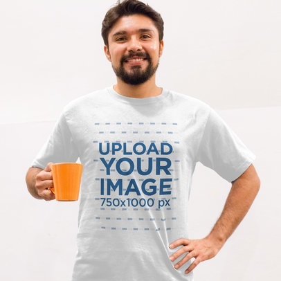 Young Hispanic Guy Wearing a Round Neck Tshirt Template While Holding a Cup of Coffee Against a White Wall a15523