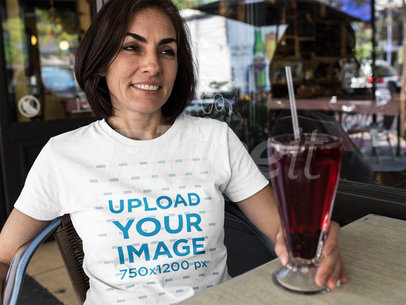 Smiling Woman Having a Juice at a Restaurant While Wearing a Round Neck Tee Mockup a15880