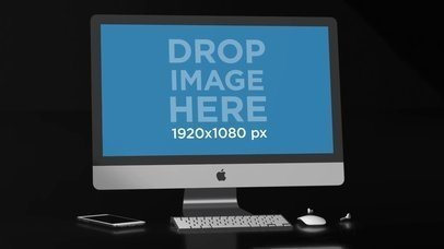 Video of an iMac Lying in a Black Room Near an iPhone and Earpads a15827
