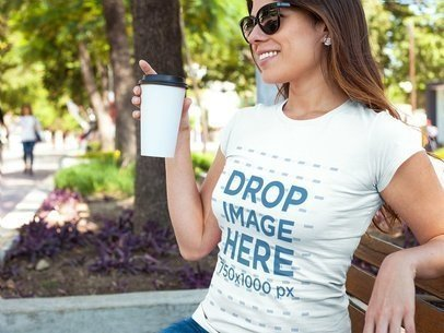 T-Shirt Mockup of a Woman Having a Coffee at a Park a7734
