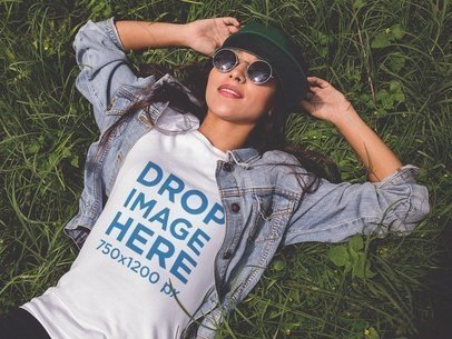 Mockup of a Trendy Girl Wearing a T-Shirt Lying in the Grass a11735