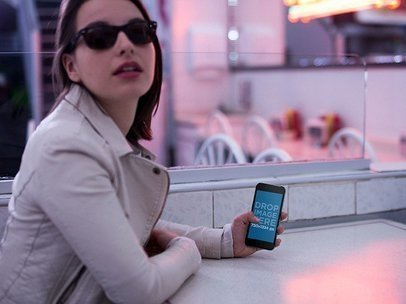 Template Of A Young Woman Wearing Sunglasses While Inside Of A Diner Restaurant With Red Lights Holding Her iPhone a13996