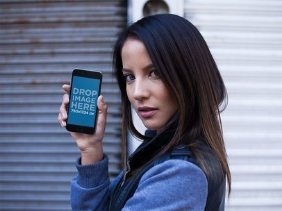 Mockup Of A Beautiful Woman In An Urban Environment Looking At The Camera While Showing An iPhone 6 In Portrait Position a14037