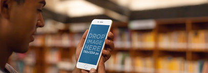 Mockup of a Male Student Using an iPhone 6 at his School Library a4902